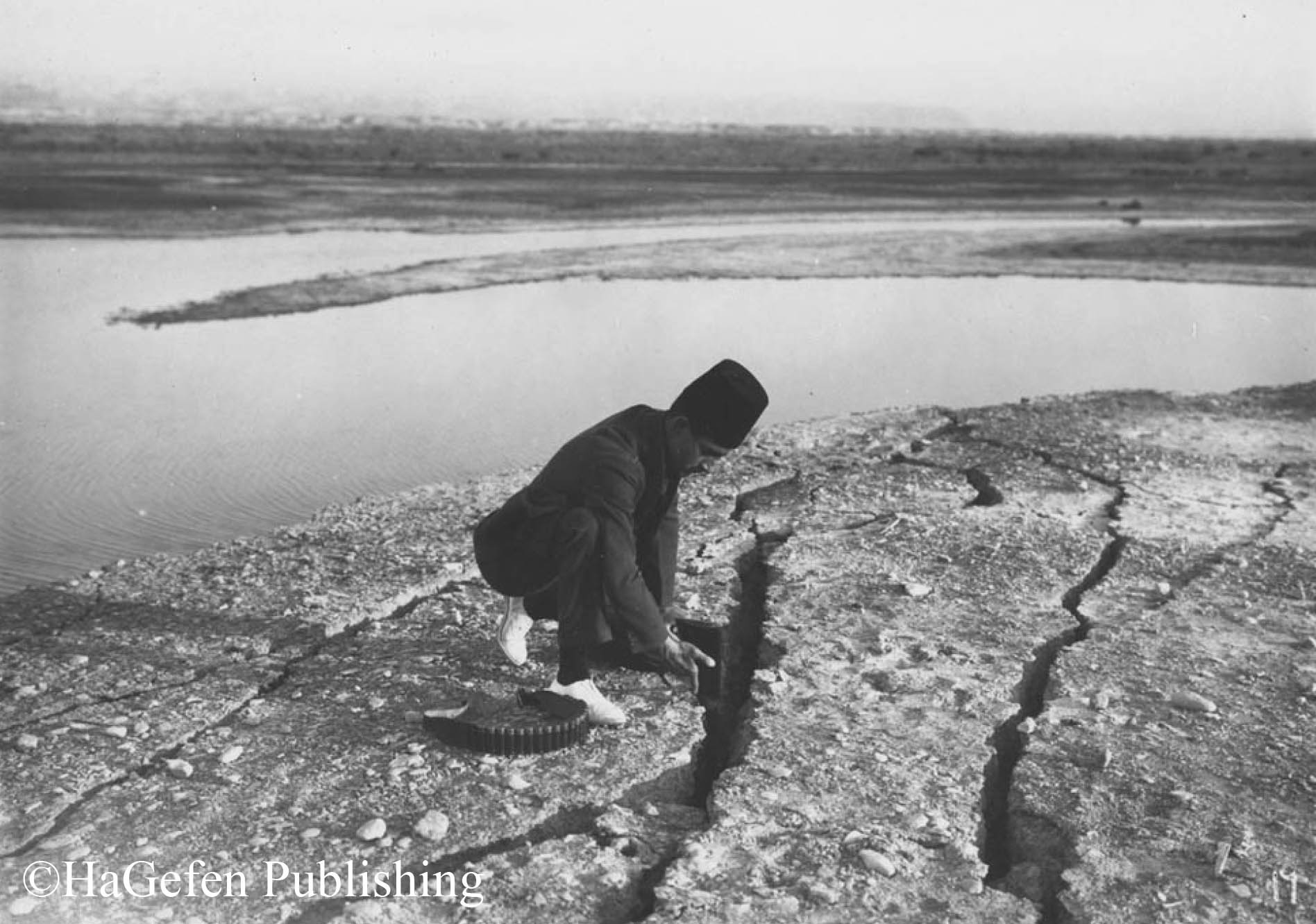 Dead Sea area after earthquake. A man holding rifle  in the carck.11/7/1927